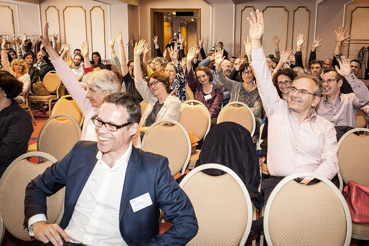 Managers raising their arm participating in a seminar at Dream Castle Hôtel in Marne-La-Vallée photographed by Denis Dalmasso french photographer