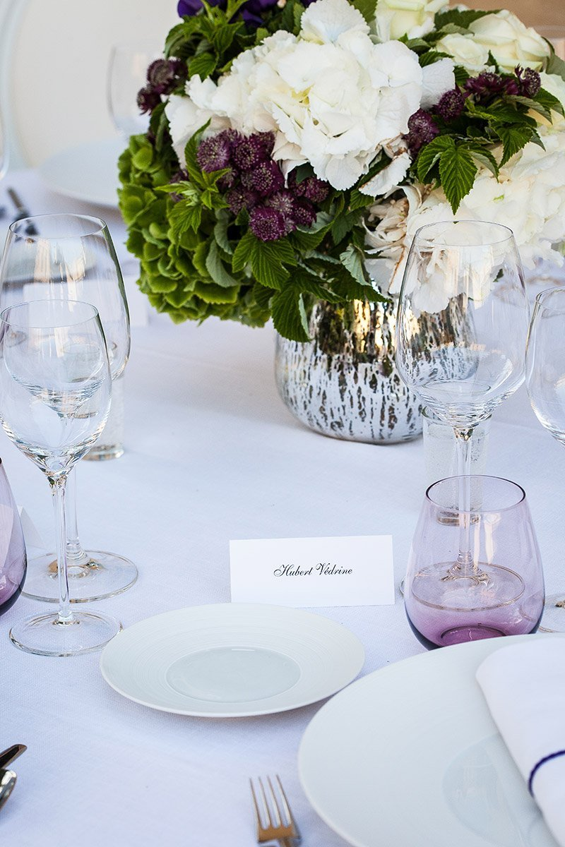 Detail of a dinner table with the name of Hubert Vedrine on a paper in front of plates and glasses