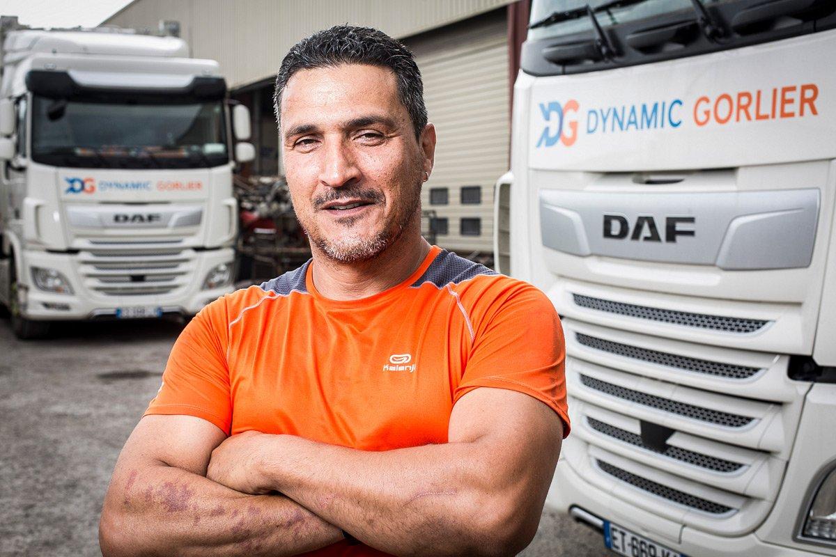 Portrait d'un chauffeur routier devant les camions de la société Dynamic Gorlier
